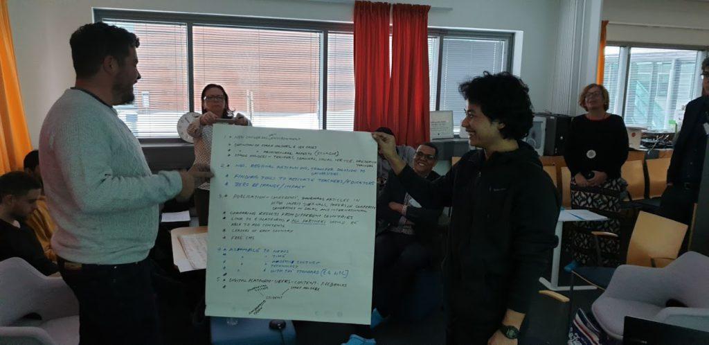 """Primera reunión del proyecto """"Smart Ecosystem for Learning and Inclusion"""". Dos de los integrantes del proyecto muestran un papel con los resultados de unos de los talleres realizados"""